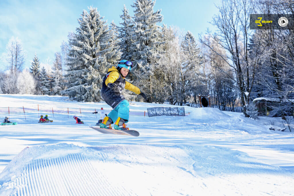 Snowboardista skákající ollie na skoku na Beany Snwoboard Campu