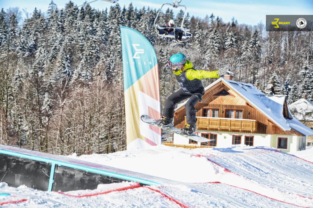 Snowboardista skáče na skoku během výuky Little Trees Snowboard School