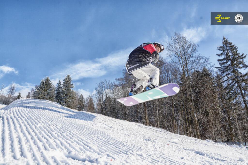 Snowboardista skáče ollie během výuky od Little Trees Snowboard školy