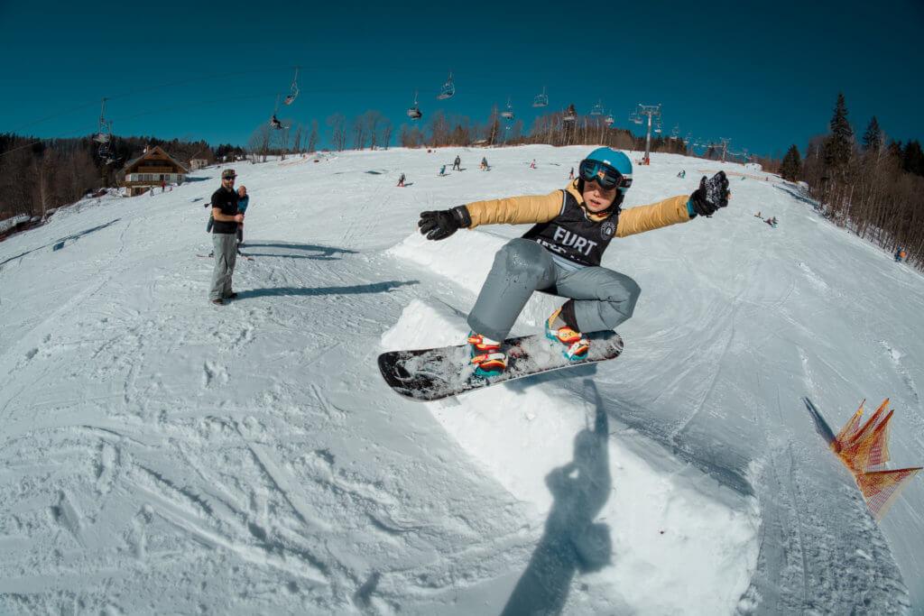 Snowboarder jumping on kicker at Beany snowboard kemp Little Trees School